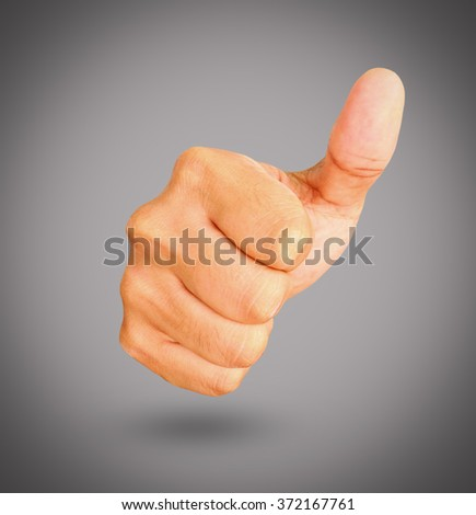 Thumbs Up on gray background. - stock photo
