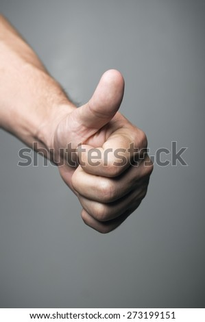 Thumbs up over a gray background