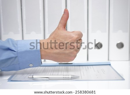 thumbs up over signed contract and binders - stock photo