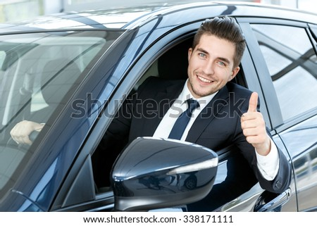 Thumbs up. Portrait of a happy businessman showing thumbs up sitting in his new car  - stock photo