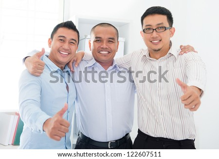 Thumbs up Southeast Asian businessmen standing in office - stock photo