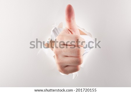 Thumbs up through paper - stock photo