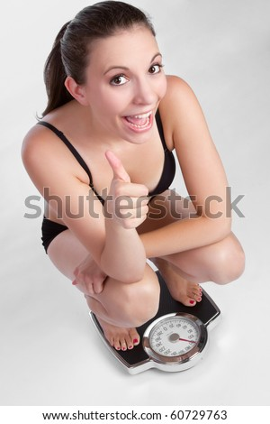 Thumbs up weight loss woman - stock photo
