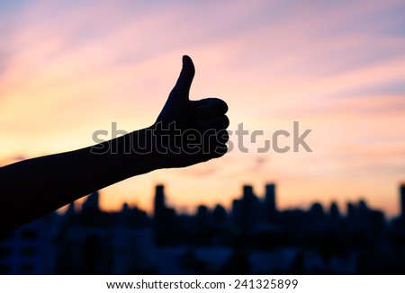 Thumbs up with city background - stock photo