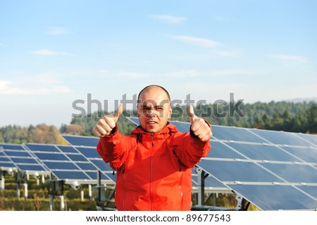 Thumbs up, young engineer at solar panels field - stock photo