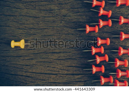 thumbtacks pinned arrange to symbolize on wooden table to be different or leadership or bravery with copy space (vintage tone) - stock photo