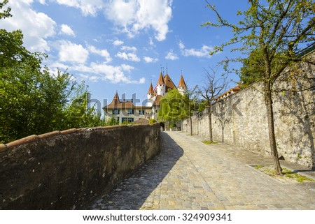 THUN, SWITZERLAND - SEPTEMBER 08, 2015: A cobbled road leads to the castle Thun. The castle was built in the 12th century, nowadays it houses the Thun Castle museum - stock photo