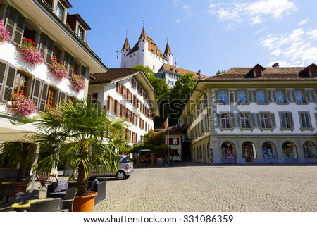THUN, SWITZERLAND - SEPTEMBER 08, 2015: The famous Thun Castle towering over the townhouses of the Town Hall Square. The castle was built in the 12th century, nowadays it houses the Thun Castle museum - stock photo