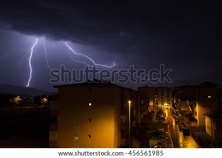 Thunder and bright lightning in town, summer storm, dangerous natural phenomena. - stock photo