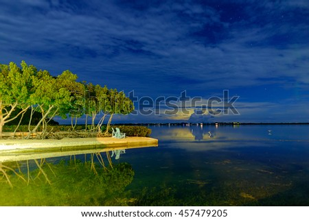 Thunder and lighting over Big Pine Key as the sky remains star studded over Little Torch Key in the Florida Keys - stock photo