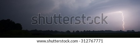 Thunder and lightning at the end of a hot and moistly summer day in the Netherlands - stock photo