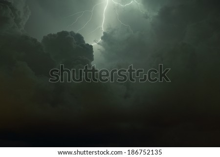 Thunderbolt and Lightning. Lightning flash illuminating the clouds on a dark night. Graduated shot from light to dark top to bottom. Shot has an almost religious quality. - stock photo