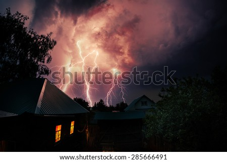 Thunderbolt over the house and dark stormy sky on the background - stock photo