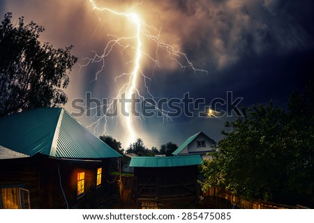 Thunderbolt over the house with dark stormy sky on the background and moon shining through the cloud - stock photo