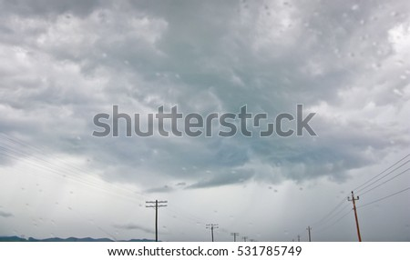 Thundercloud over the power lines through the raindrops on the objective lens.