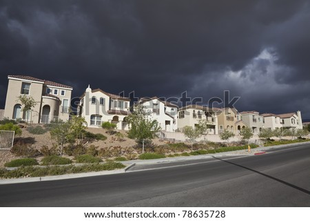 Thunderstorm approaches a brand new row of suburban homes in a southern Nevada desert community. - stock photo