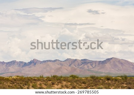 Thunderstorm clouds gathering above Arizona mountains in desert - stock photo