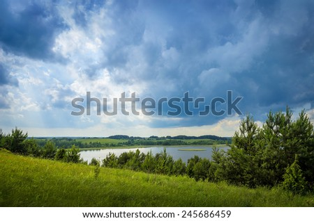 thunderstorm clouds over the lake - stock photo