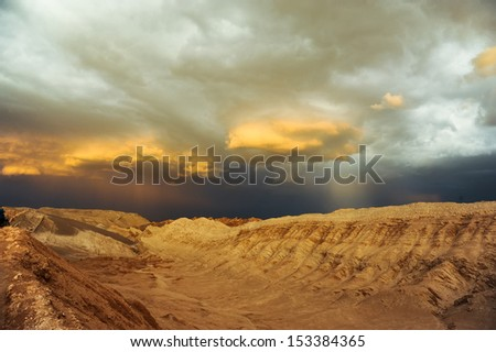 Thunderstorm developing over sand dune in Valle De La Luna in the Atacama Desert near San Pedro de Atacama, Chile. The Atacama Desert is one of the driest places on earth, and these storms are rare. - stock photo