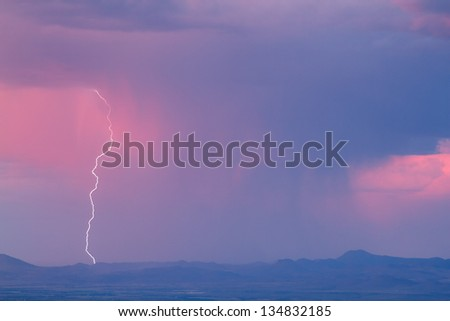 Thunderstorm with lightning and heavy rainclouds at sunset - stock photo