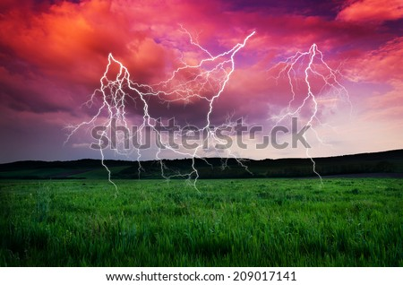 Thunderstorm with lightning in green meadow