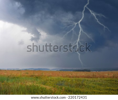 Thunderstorm with lightning in meadow. Dark ominous clouds. - stock photo