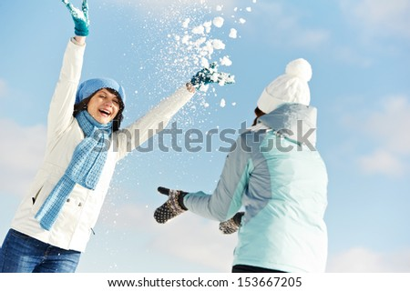Thwo girl having fun with snow in winter outdoors - stock photo