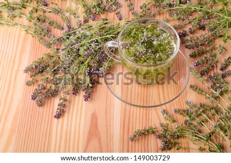 Thyme flowers and herbal tea in gluss cup on a wood table background