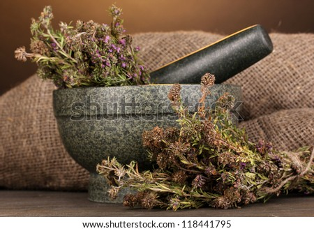 Thyme herb and mortar on wooden table on brown background - stock photo