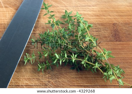 thyme on a chopping board with knife