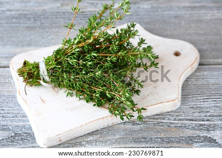 Thyme on a white chopping board, spice - stock photo
