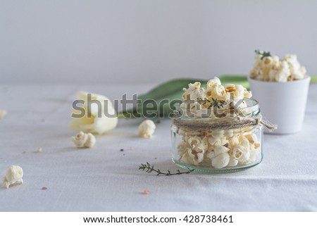 Thyme popcorn with pink salt and black pepper. Thyme popcorn with crushed pink Himalayan salt and black pepper. Served in a small glass jar. Copy space available.  - stock photo