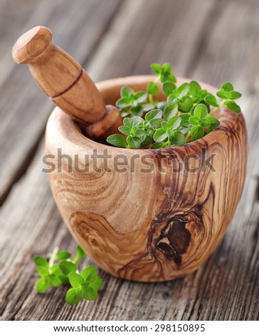 Thyme spices in a wood olive mortar - stock photo