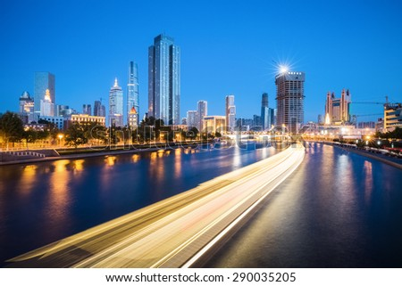 tianjin at night , light trails from a cruise ship on the haihe river - stock photo