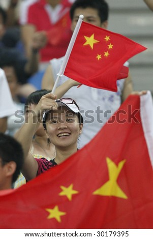 TIANJIN, CHINA - AUGUST 6: A young woman shows her support for the Chinese women's soccer team prior to a match between China and Sweden at the Beijing Olympic Games August 6, 2008 in Tianjin, China. - stock photo