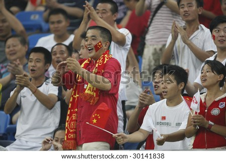 TIANJIN, CHINA - AUGUST 6:  Chinese supporters cheer their team prior to the start of a women's soccer match between China and Sweden at the Beijing Olympic Games August 6, 2008 in Tianjin, China. - stock photo