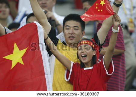 TIANJIN, CHINA - AUGUST 6:  Fans show their support for the Chinese women's soccer team prior to a match between China and Sweden at the Beijing Olympic Games August 6, 2008 in Tianjin, China. - stock photo