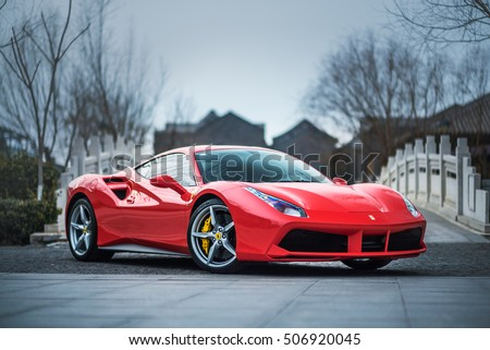 TIANJIN, CHINA - FEB 27, 2016: A red Ferrari 488 GTB parked in front of a stone bridge. The Ferrari 488 is an Italian sports car produced since 2015, powered by a 3.9-litre twin-turbocharged V8.