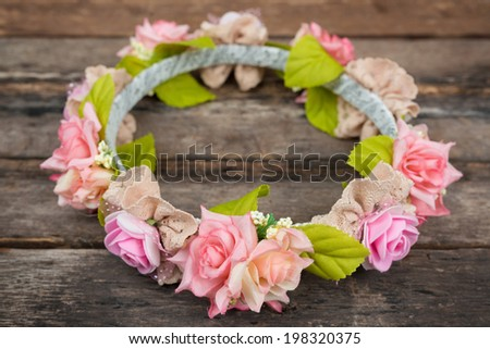 tiara of artificial roses on wooden background. - stock photo