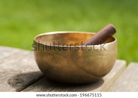tibetan bowl on wood with green background - stock photo