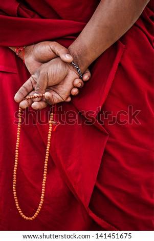 Tibetan Buddhism - prayer beads in Buddhist monk hands. Ladakh, India - stock photo