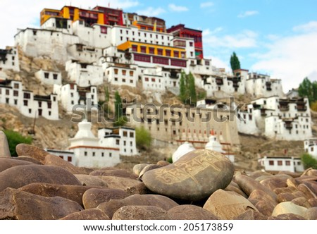 Tibetan Buddhist Mani Stones with carved mantras against the blurred background of ancient Thiksey monastery (Gompa) - Leh district, Ladakh range, Himalaya, Jammu & Kashmir, Northern India  - stock photo