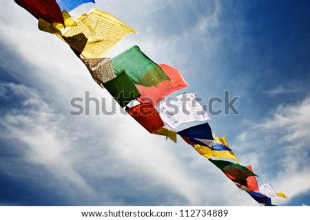 tibetan flags with mantra on sky background - stock photo