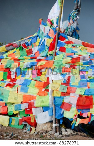 Tibetan prayer flags tied to a white Buddhist stupa in the Himalayas, Tibet, China - stock photo