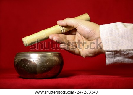 Tibetan singing bowl on the red background. - stock photo