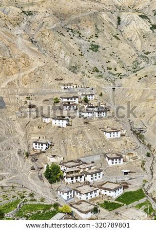 Tibetan style white houses located on steep slope - stock photo
