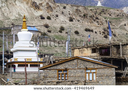 Tibetan village in Himalayas, Nepal with snowcapped mountains in the background - stock photo