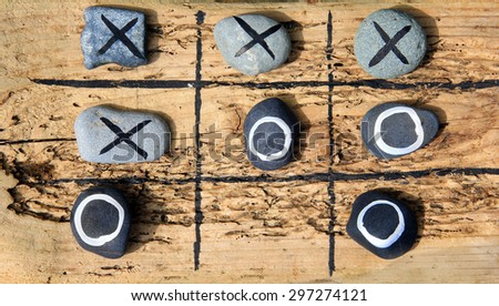 Tic tac toe game made from drift wood and rocks for outdoor garden play.  - stock photo