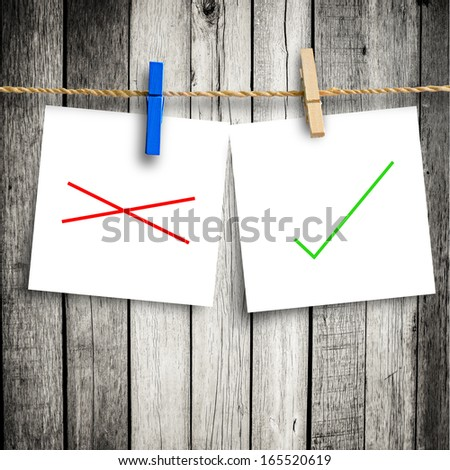 tick and cross  on note paper attach to rope with clothes pins on wooden background  with clipping path - stock photo