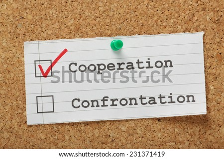Tick boxes for cooperation versus confrontation on a cork notice board, with a red tick for the right choice in the cooperation box - stock photo